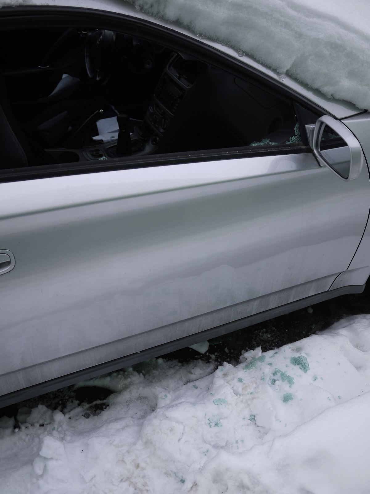 Car buried under snow and suffered a broken window